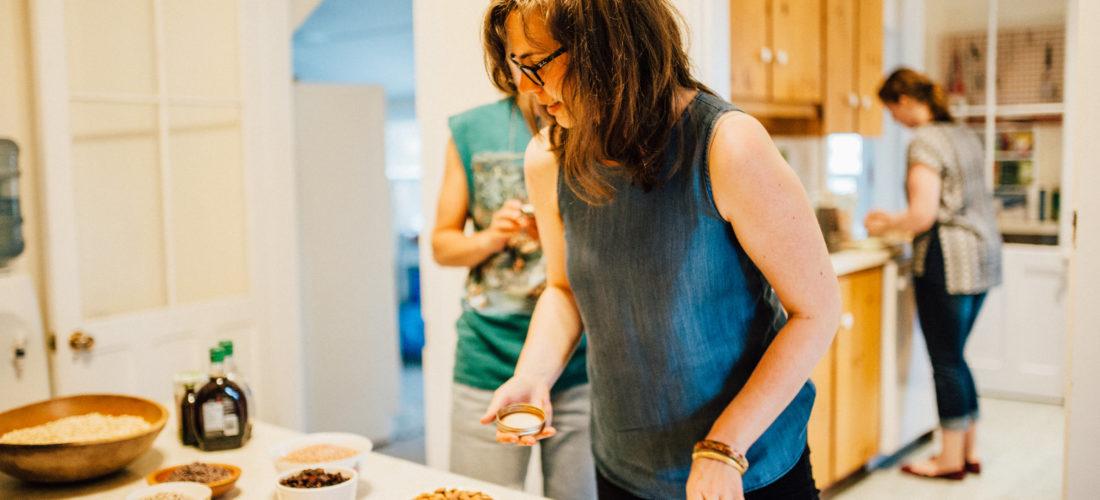 Women in kitchen preparing food with tenderness.